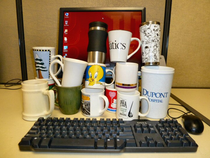 Lots of coffee cups in front of the computer